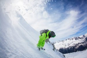 Snowboarder riding down the mountain in the powder